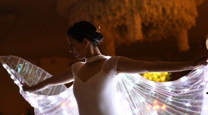 Dansare med LED-vingar uppträder i en magisk show