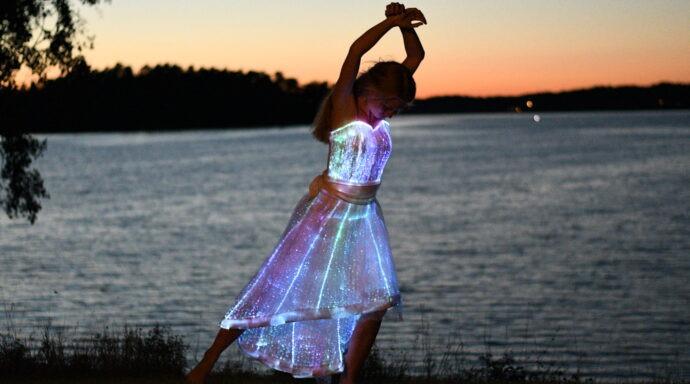Dansare med ljusklänning uppträder i en magisk show