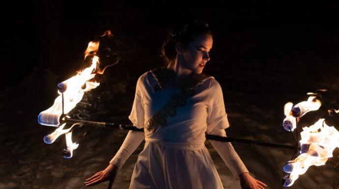 Elddansare med drakstav uppträder i en vacker eldshow