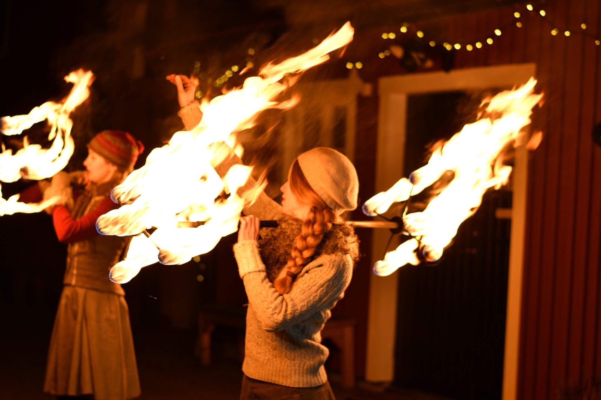 Två elddansare med drakstav på vintermarknad