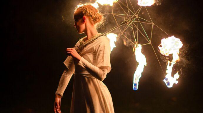 Elddansare med paraply uppträder i en vacker eldshow