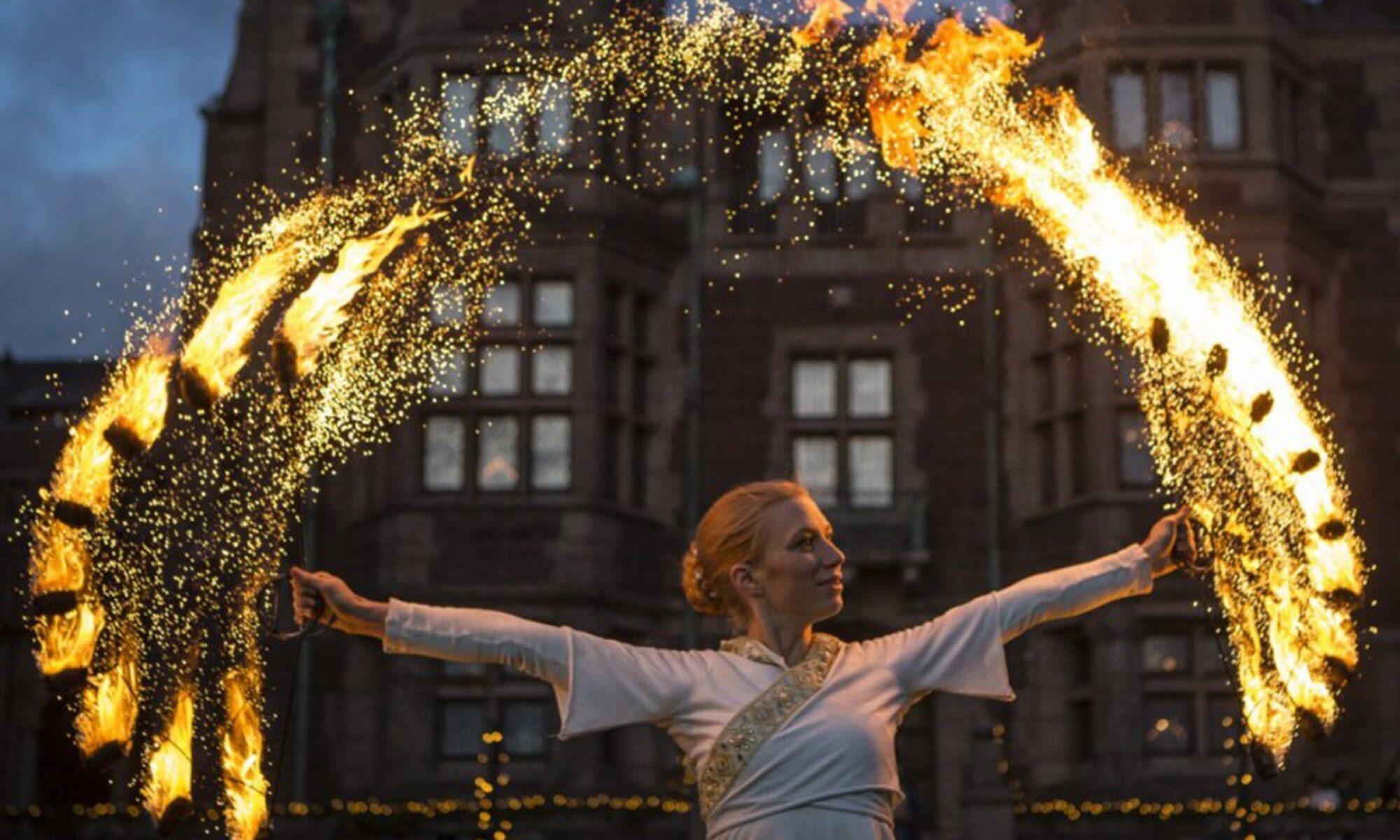 Elddansare med solfjädrar uppträder i en vacker eldshow